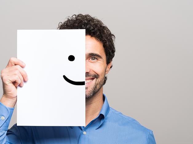 Homem sorrindo com metade do rosto coberto por um desenho de um rosto feliz.